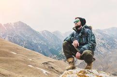 O moderno farpado cansado com os binóculos em suas mãos senta-se em uma pedra entre as montanhas e olha-se para fora na distância Fotos de Stock Royalty Free