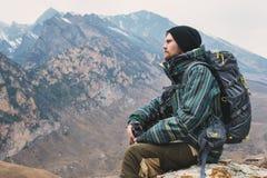 O moderno farpado cansado com os binóculos em suas mãos senta-se em uma pedra entre as montanhas e olha-se para fora na distância Imagem de Stock