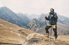 O moderno farpado cansado com os binóculos em suas mãos senta-se em uma pedra entre as montanhas e olha-se para fora na distância Fotos de Stock