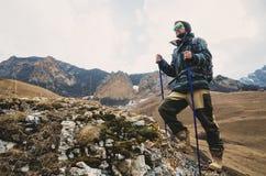 O moderno farpado cansado com os binóculos em suas mãos senta-se em uma pedra entre as montanhas e olha-se para fora na distância Foto de Stock Royalty Free