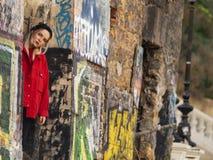 O moderno louro da moça ativa está perto das ruínas com as paredes nos grafittis foto de stock royalty free