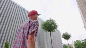 O moderno novo de Readhead no chapéu anda a rua fotos de stock