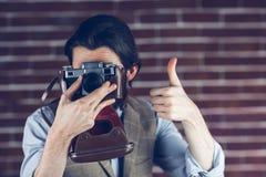 O moderno que mostra os polegares levanta o gesto ao fotografar imagens de stock royalty free