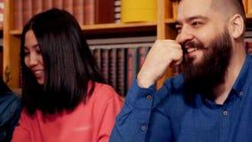O moderno senta e ajusta sua barba na tabela com seus amigos favoritos em um café bonito