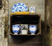 O moedor de café velho com os pratos no armário na parede Imagem de Stock