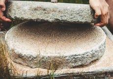 O moinho de mão antigo da pedra do Quern com grão O homem aumenta a roda superior de uma pedra de moer grão-enchida Moedura velha imagens de stock