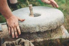 O moinho de mão antigo da pedra do Quern com grão O homem mói a grão na farinha com a ajuda de uma pedra de moer ` S dos homens fotografia de stock royalty free