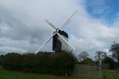 O moinho de vento velho senta o abandono entre árvores e campos vazios Fotos de Stock