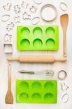 O molde e as ferramentas do bolo para o queque, o queque e a cookie cozem no fundo de madeira branco Foto de Stock Royalty Free