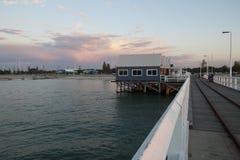 O molhe é um ponto de encontro para os locals que pescam e nadam na noite fotografia de stock
