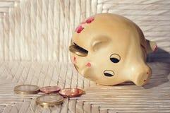 O moneybox do porco com Euro inventa no fundo de madeira branco Fotografia de Stock Royalty Free