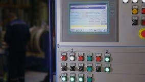 O monitor, o écran sensível, o painel industrial com dados e o controle abotoam-se em uma planta industrial filme
