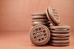O montão de cookies dos pedaços de chocolate encheu-se com as mentiras de creme brancas da baunilha na superfície de madeira do m fotos de stock