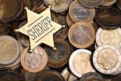 O montão de uma e dois euro- moedas com um xerife star imagens de stock royalty free
