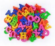 O montão do plástico coloriu letras do alfabeto em um branco Imagens de Stock