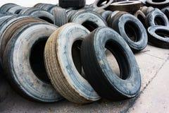 O montão do pneu de carro alinha na terra do cimento, pneus usados Imagem de Stock