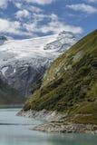 O montanhês é refletido nas águas do reservatório Mooserboden Imagem de Stock