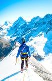O montanhista alcança a cimeira do pico de montanha Escalada e mounta Imagens de Stock