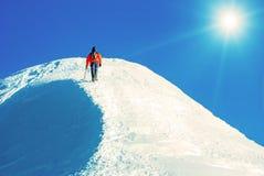 O montanhista alcança a cimeira do pico de montanha Escalada e mounta Fotos de Stock Royalty Free