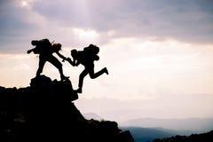 O montanhista alcança para fora a seu sócio ajudando-se montanhistas principais; Team o trabalho, os objetivos da vida e o concei foto de stock