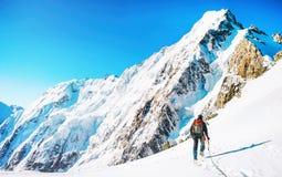 O montanhista alcança a parte superior do pico de montanha Escalada e mountaine Fotos de Stock Royalty Free
