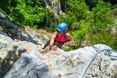 O montanhista aventuroso, corajoso da mulher na através da rota do ferrata chamou Casa Zmeului, uma atração turística popular per fotografia de stock