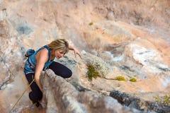 O montanhista bonito louro no terreno rochoso faz o movimento difícil fotografia de stock