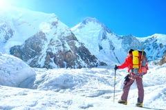 O montanhista com trouxas alcança a cimeira do pico de montanha Sucesso, liberdade e felicidade, realização nas montanhas Esporte foto de stock