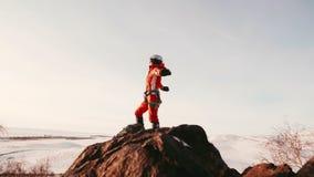 O montanhista da menina em um terno alaranjado brilhante está no pico da montanha, espalhou suas mãos aos lados e olhou-as vídeos de arquivo