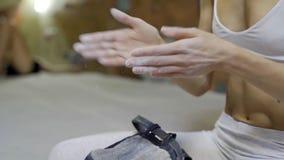 O montanhista da mulher está riscando as mãos com pó branco do giz antes da escalada no gym de escalada interno Mulher que prepar filme