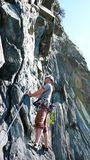 O montanhista de rocha masculino no início de um passo íngreme contempla seu próximo passo Fotografia de Stock Royalty Free