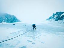O montanhista do homem escala as montanhas com uma corda na geleira O conceito da recreação e da aventura extremas foto de stock royalty free