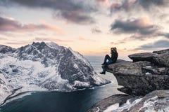 O montanhista do homem que senta-se na rocha do cume com a montanha sightseeing da neve ryten sobre a montagem imagem de stock