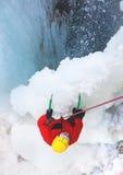 O montanhista escala no gelo perto da cachoeira foto de stock