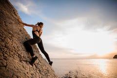 O montanhista extremo fêmea conquista a rocha íngreme contra o por do sol sobre o rio foto de stock