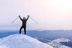 O montanhista exulta, alcançando a parte superior da montanha Foto de Stock