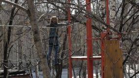 O montanhista fêmea novo anda pela ponte de corda do pendente em cordas altas percorre no parque extremo Conceito da escalada vídeos de arquivo