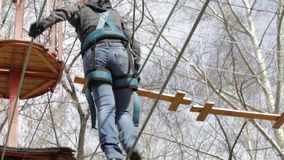 O montanhista fêmea novo anda pela ponte de corda do pendente em cordas altas percorre no parque extremo Conceito da escalada filme