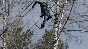 O montanhista fêmea novo anda pela ponte de corda do pendente em cordas altas percorre no parque extremo Conceito da escalada video estoque