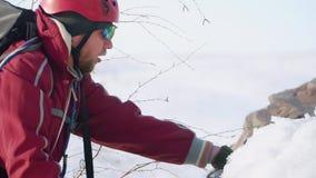 O montanhista farpado quebra a neve densa do machado de gelo para fixar o equipamento é vestido calorosamente, nele uma trouxa e  filme