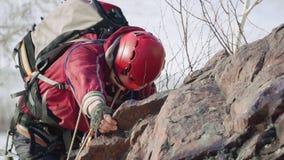O montanhista firmemente agarra sua mão sobre a borda da rocha e aumenta acima está vestindo uma trouxa pesada, equipamento video estoque