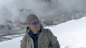 O montanhista olha a parte superior com que veio para baixo, e exulta-a que podia a escalar O Monte Elbrus, Cáucaso vídeos de arquivo