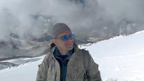 O montanhista olha a parte superior com que veio para baixo, e exulta-a que podia a escalar O Monte Elbrus, Cáucaso filme