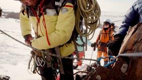 O montanhista passa um outro carabiner com uma corda, preparam e amarram o equipamento à pedra video estoque