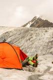 O montanhista tem um resto encontrar-se na barraca na geleira foto de stock royalty free