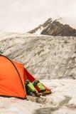 O montanhista tem um resto encontrar-se na barraca na geleira imagens de stock royalty free