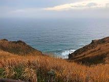O monte do cabo, grama do outono e o mar com nebuloso Fotografia de Stock