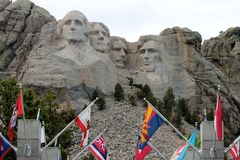 O Monte Rushmore com as bandeiras no primeiro plano Foto de Stock Royalty Free