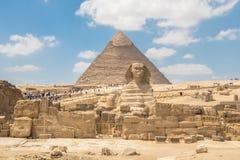 O monumento da esfinge com o corpo de uma cabeça do leão e de um pharaoh na pirâmide do fundo de Chephren, Egito imagens de stock