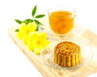 O mooncake delicioso e o chá quente com um amarelo florescem elementos Fotos de Stock